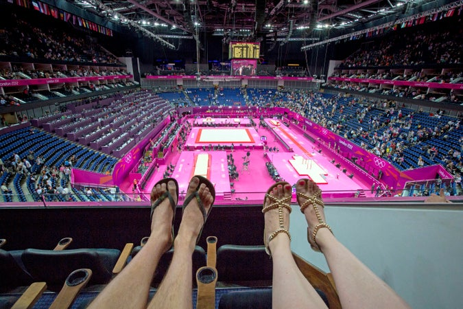 View of couple's feet watching Olympic gymnastics at Millennium Dome, London, England