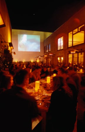 Diners enjoy a screening and a meal on the patio in the Foreign Cinema Restaurant, San Francisco, USA