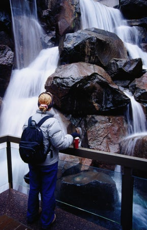 A woman watching the waterfalls at Waterfall Park in Pioneer Square, Seattle, USA