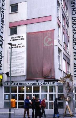 Checkpoint Charlie Museum covered by tattered Soviet flag on Friedrichstr, Kreuzberg, Berlin, Germany
