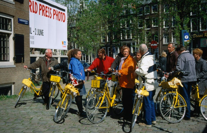 A group of people meet for a bicycle tour of the city on distinctly yellow bicycles, Amsterdam, The Netherlands