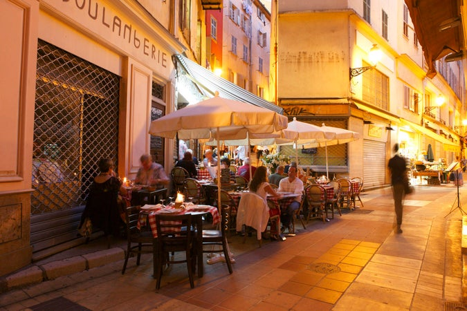 Diners sitting outside L'Escalinada at night, Nice, France