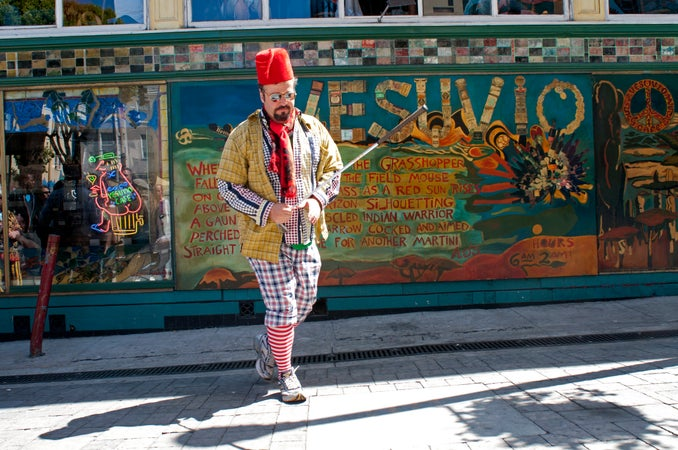 Man in costume playing golf in Jack Keroauc Alley in front of Vesuvios, San Francisco, USA