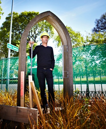 Reverend Craig Dixon standing in doorway of old cathedral that was demolished after earthquake, Christchurch, New Zealand