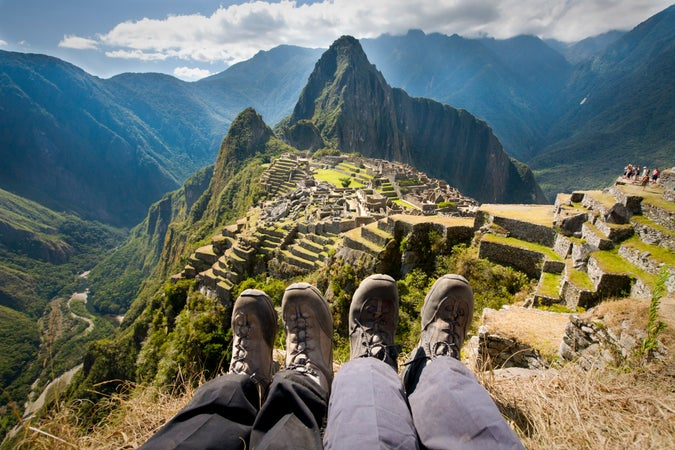 View of couple's feet sitting on stone terrace overlooking Huayna Picchu, Cuzco, Peru