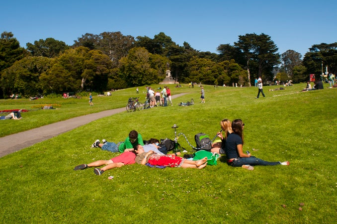 Young people relaxing in grass at Golden Gate Park, San Francisco, USA