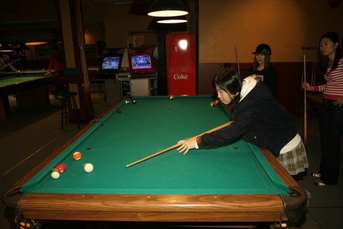 Young women shooting pool at Commodore Lanes and Billiards, Vancouver, Canada