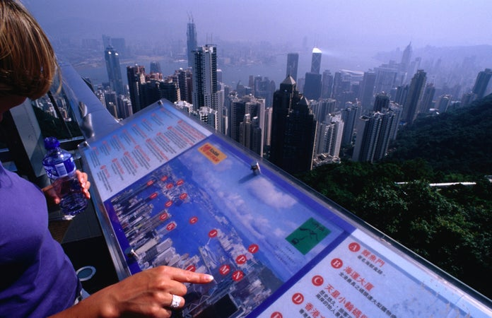 A tourists and a location map at the Victoria Peak Lookout and the city of Hong Kong below, Hong Kong, China
