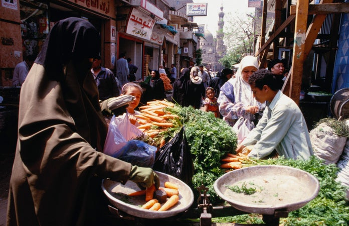In view of the minaret of the Mosque Al-Hakim are the markets of Sugar street in Islamic Cairo made famous by the writings of Naguib Mahfouz, Cairo, Egypt