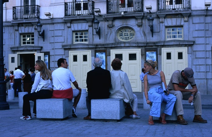 People rest in front of Madrid's Teatro Espanol on the Plaza de Santa Ana, Madrid, Spain