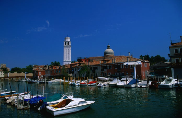 Boats along canal and Cathedral San Pietro di Castello, Venice, Italy