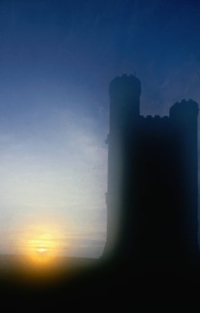 The Cotswolds: the sun rising behind Broadway Tower, a crenellated 18th century folly that stands above the town, Broadway, United Kingdom