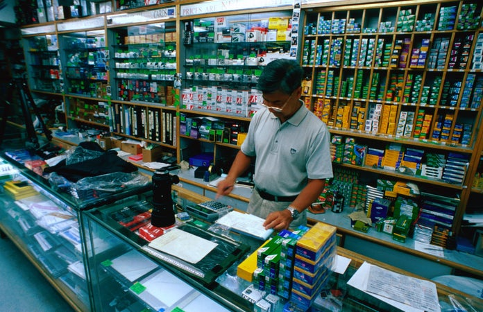 A shop assistant behind the counter at Photo scientific camera shop on Stanley Street, Soho, Hong Kong, China