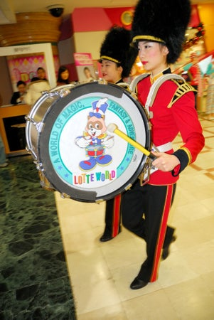 Young woman beats drum as band walk through mall and shop at Lotte World, Jamsil, Seoul, South Korea