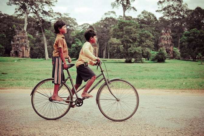 Two local children riding bicycle on grounds of Angkor Wat, Temples of Angkor, Cambodia