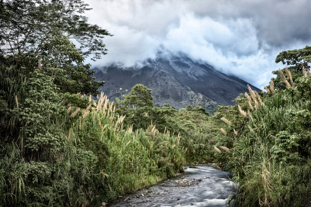 Stream running through forest with Arenal Volcano in background.