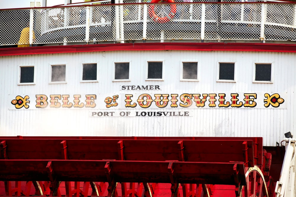 Painted sign above the paddles of the 'Belle of Louisville' on Ohio River.