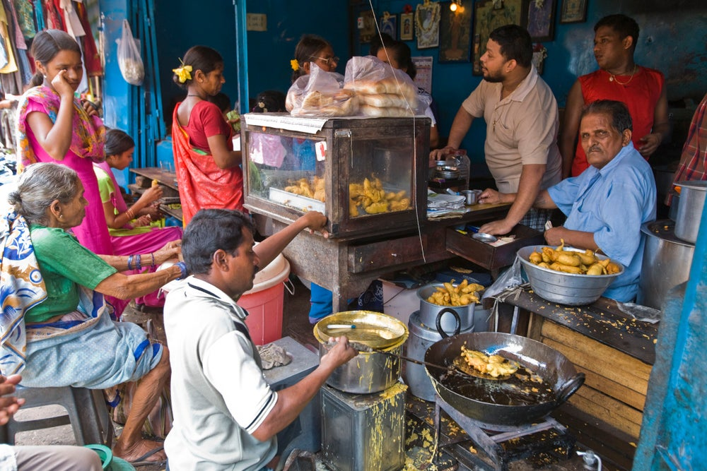 Food stall, cooking chilli fritters and serving bhaji pau, at Mapusa Market.
