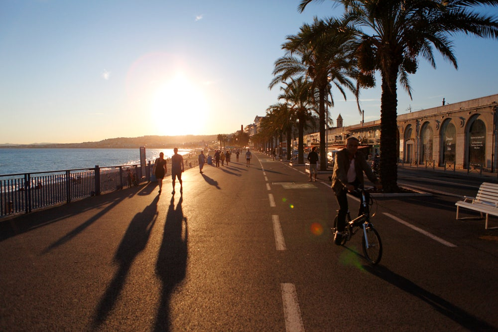 People on palm lined Promenade des Anglais.