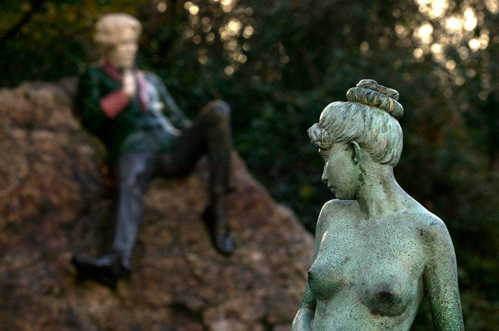 Bronze statue with Oscar Wilde memorial in background, Merrion Square.