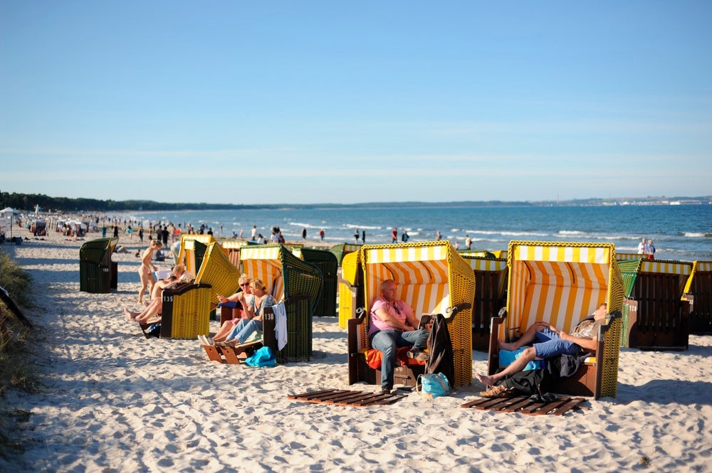People sitting in Strandkorb chairs on beach.